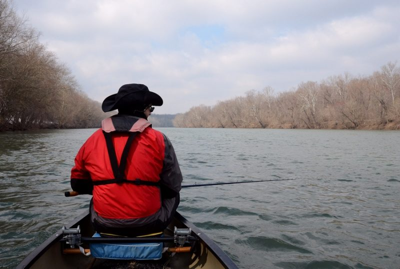 angler fishing for muskie in a canoe