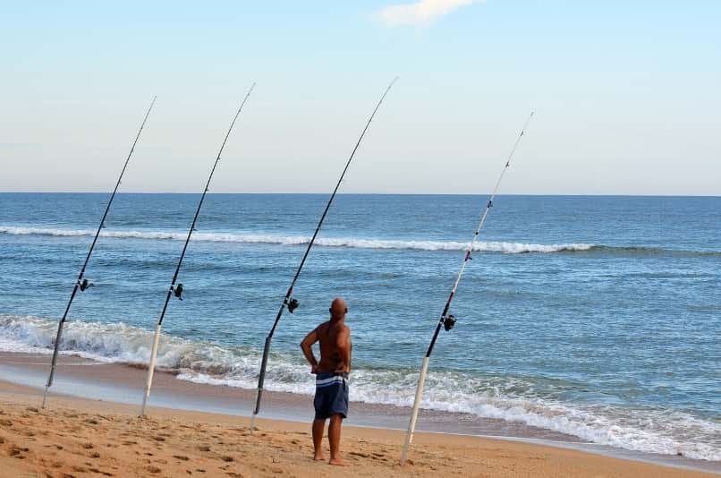 4 surf fishing rods watched by fisherman
